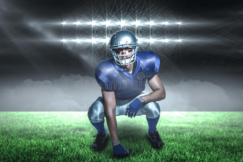 Composite image of american football player in uniform crouching with 3d. American football player in uniform crouching against spotlights with copy space 3d stock photos