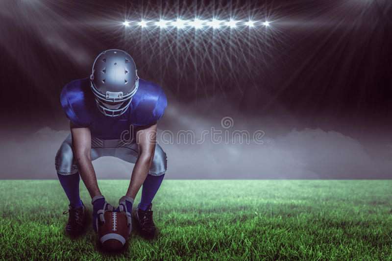 Composite image of american football player in uniform holding ball while crouching. American football player in uniform holding ball while crouching against stock photos