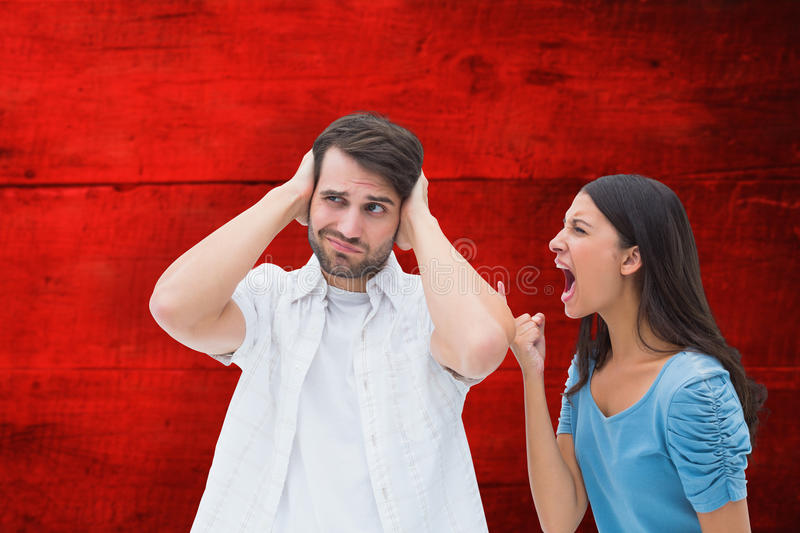 Composite image of angry brunette shouting at boyfriend. Angry brunette shouting at boyfriend against red wooden planks royalty free stock image