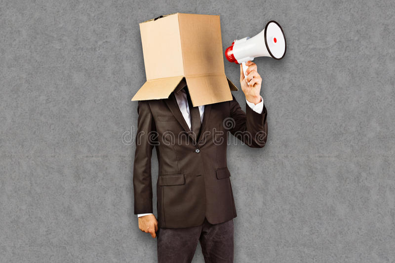 Composite image of anonymous businessman holding a megaphone. Anonymous businessman holding a megaphone against grey background stock photography