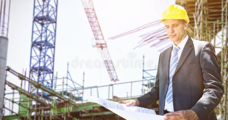 Composite image of architect holding blueprint stock photography