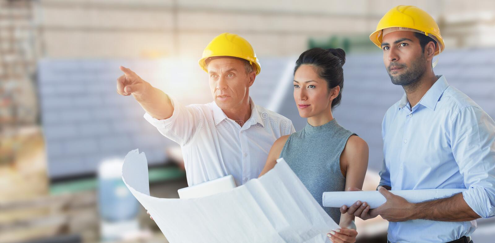 Composite image of architects looking away while holding blueprint royalty free stock image