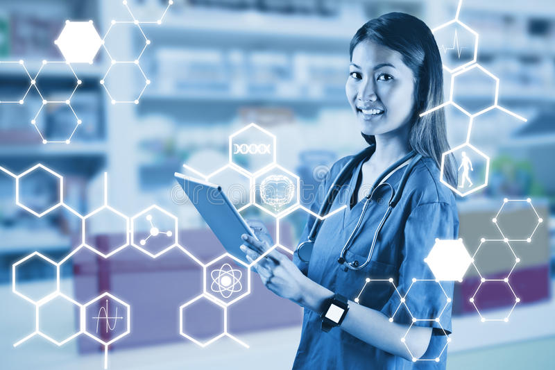 Composite image of asian nurse using tablet royalty free stock photography