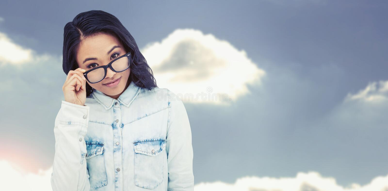 Composite image of asian woman holding eyeglasses stock image