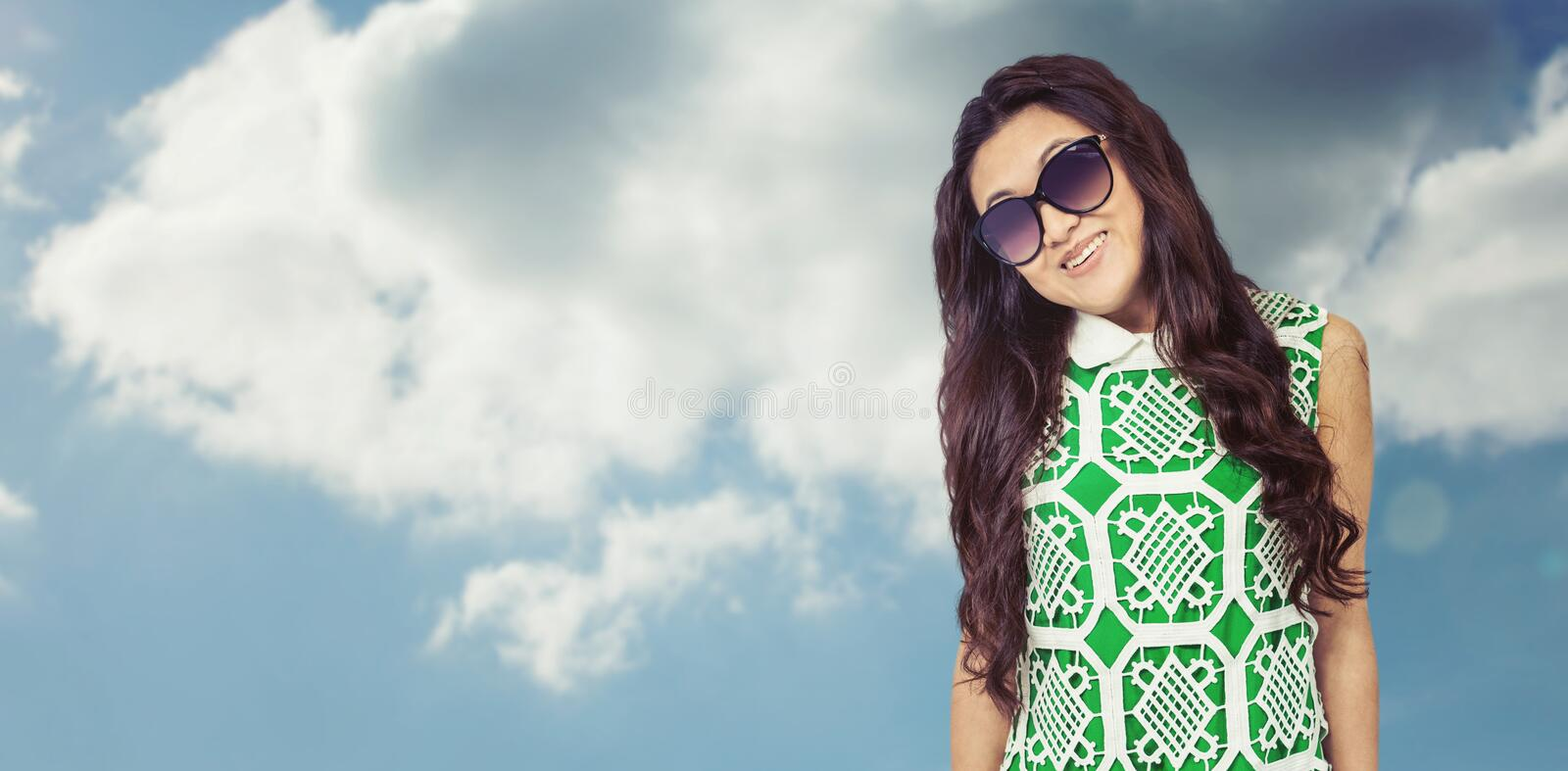Composite image of asian woman with sunglasses posing for camera royalty free stock photography