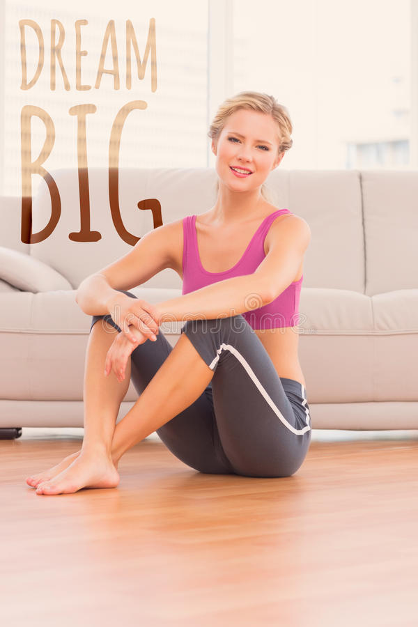 A Composite image of athletic blonde sitting on floor smiling at camera stock image