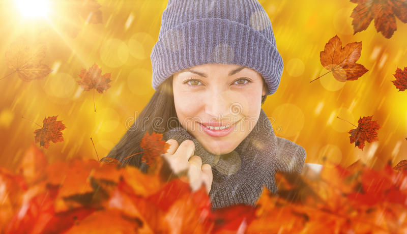 Composite image of attractive brunette looking at camera wearing warm clothes stock photos