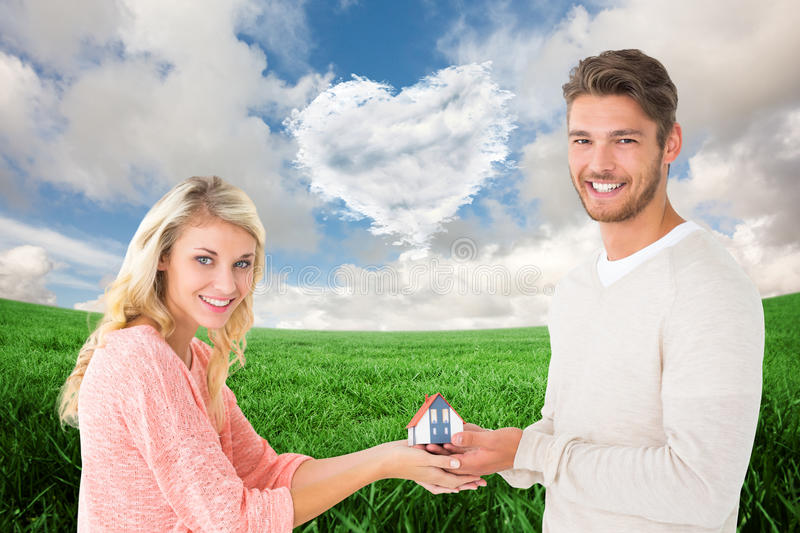 Composite image of attractive couple holding miniature house model. Attractive couple holding miniature house model against cloud heart royalty free stock images