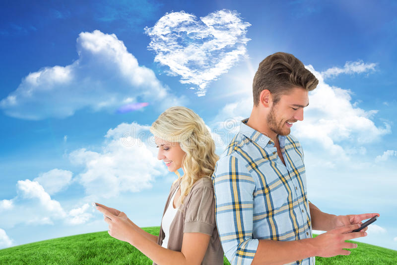 Composite image of attractive couple using their smartphones royalty free stock photography