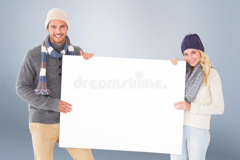 Composite image of attractive couple in winter fashion showing poster stock image