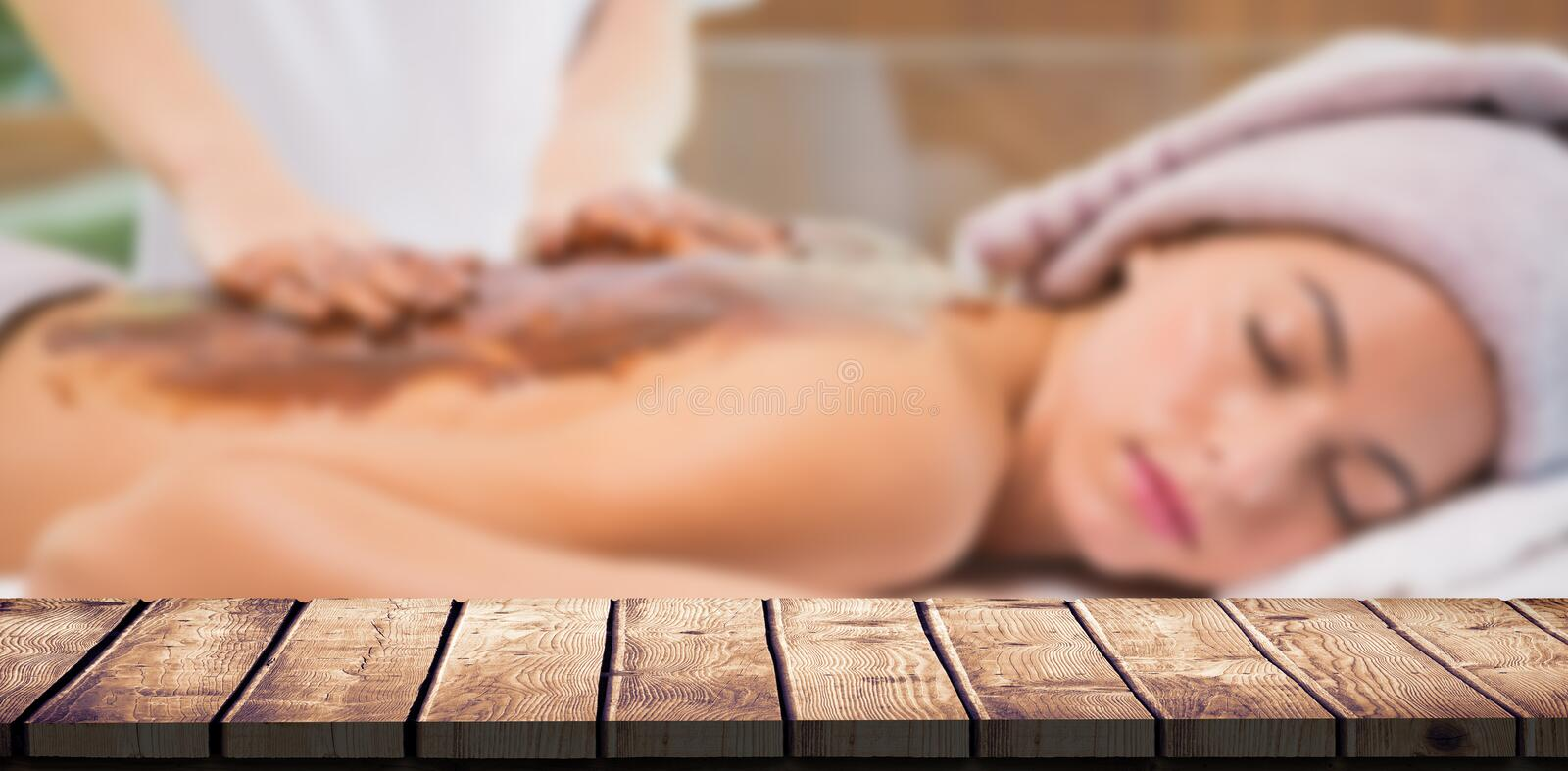 Composite image of attractive woman receiving chocolate back mask at spa center. Attractive woman receiving chocolate back mask at spa center against wooden desk stock image