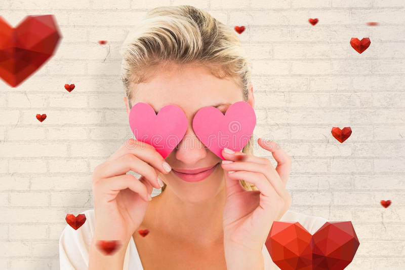 Composite image of attractive young blonde holding hearts over eyes. Attractive young blonde holding hearts over eyes against white wall royalty free stock photography