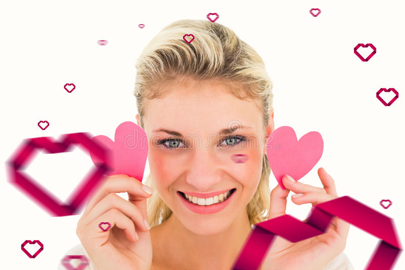 Composite image of attractive young blonde holding little hearts. Attractive young blonde holding little hearts against hearts royalty free stock image