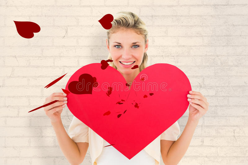 Composite image of attractive young blonde showing red heart. Attractive young blonde showing red heart against white wall royalty free stock image