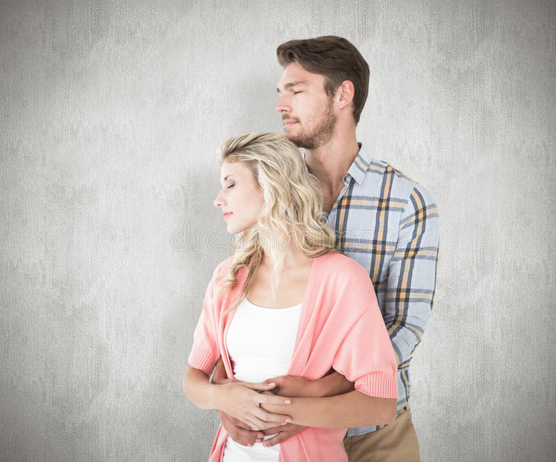 Composite image of attractive young couple embracing and smiling stock photo