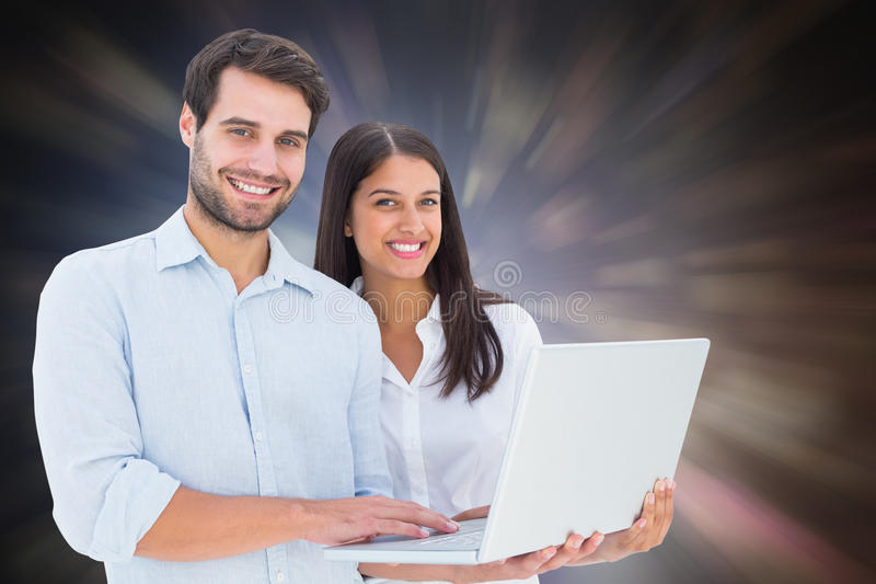 Composite image of attractive young couple holding their laptop. Attractive young couple holding their laptop against dark abstract light spot design stock photo