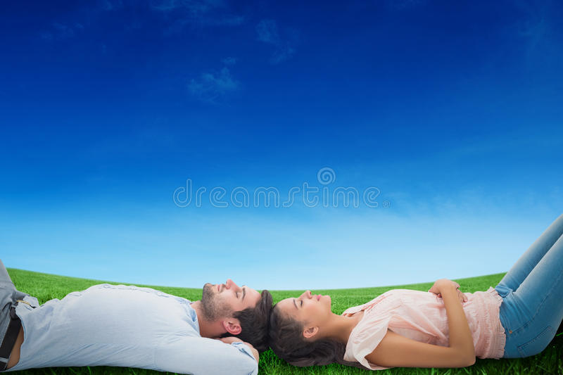 Composite image of attractive young couple lying down stock images
