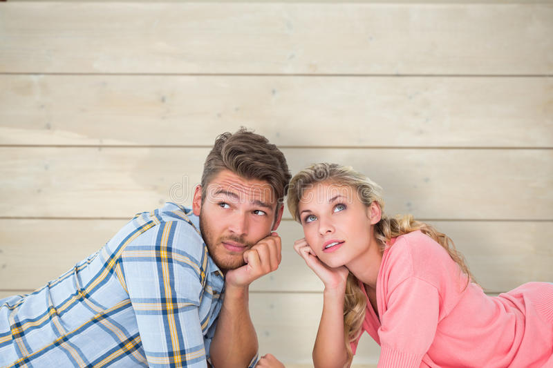 Composite image of attractive young couple lying and thinking royalty free stock photos
