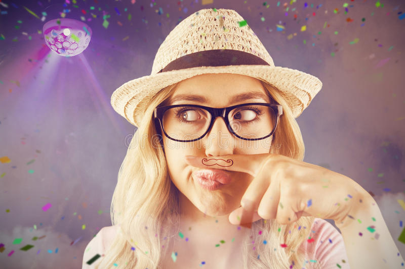Composite image of a beautiful hipster having a fake mustache stock photo