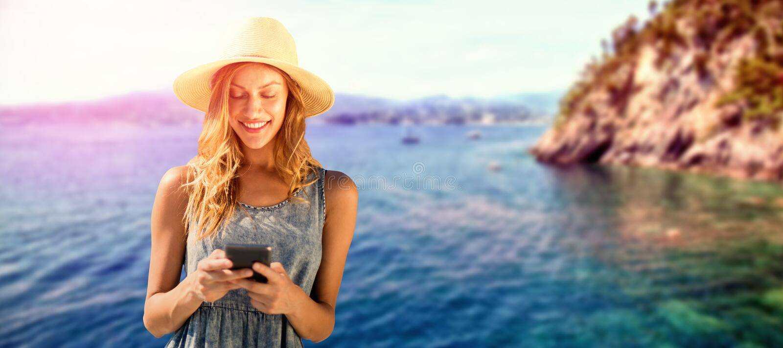 Composite image of beautiful woman using her mobile phone. Beautiful woman using her mobile phone against idyllic view of sea royalty free stock photography