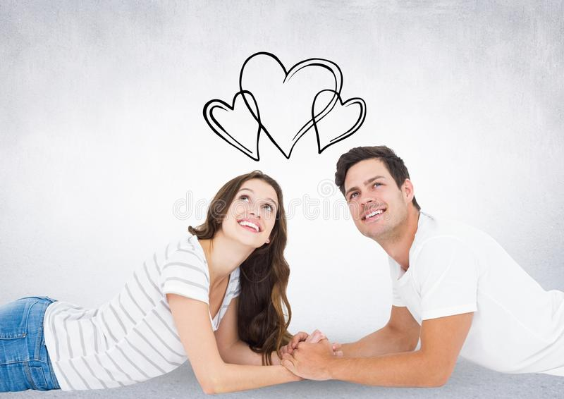 Composite image of black hearts and thoughtful couple lying on floor stock illustration