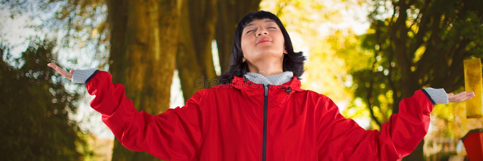 Composite image of blissful woman standing with arms outstretched. Blissful woman standing with arms outstretched against fallen leaves on field at park royalty free stock photo