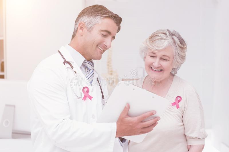 Composite image of breast cancer awareness ribbon. Breast cancer awareness ribbon against doctor and patient discussing over reports stock photography