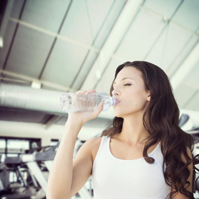 Composite image of brunette drinking water royalty free stock image