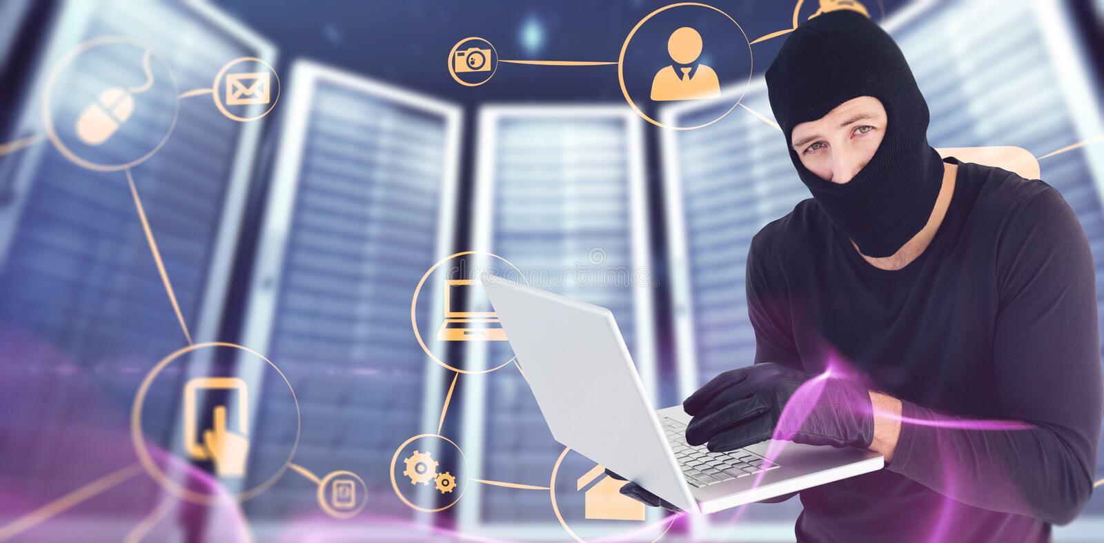Composite image of burglar standing holding laptop while looking at camera stock image