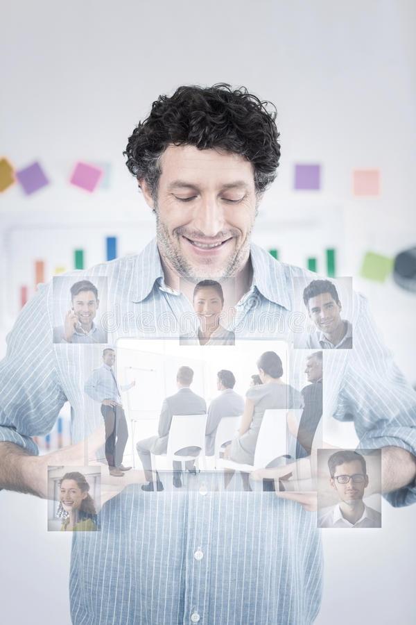 Composite image of business people having a meeting. Business people having a meeting against businessman showing digital tablet in creative office stock photo