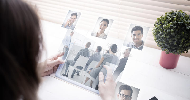 Composite image of business people having a meeting. Business people having a meeting against women using tablet at desk royalty free stock image