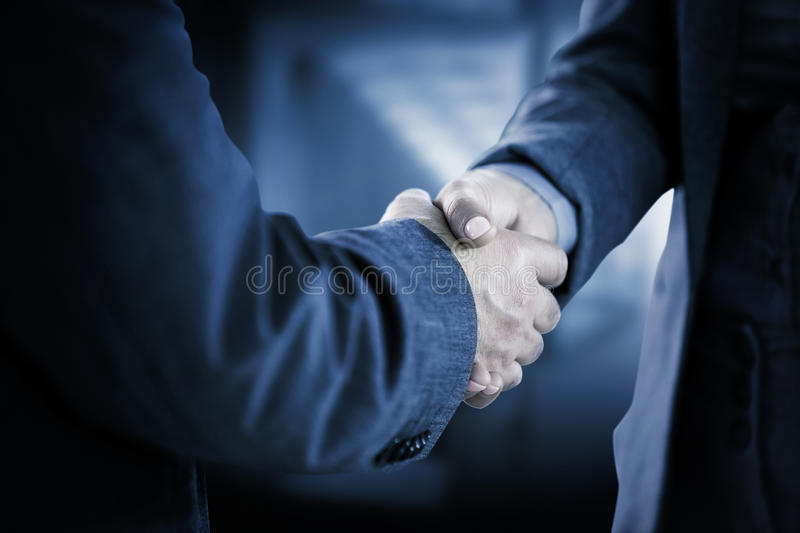 Composite image of business people shaking hands close up stock photo