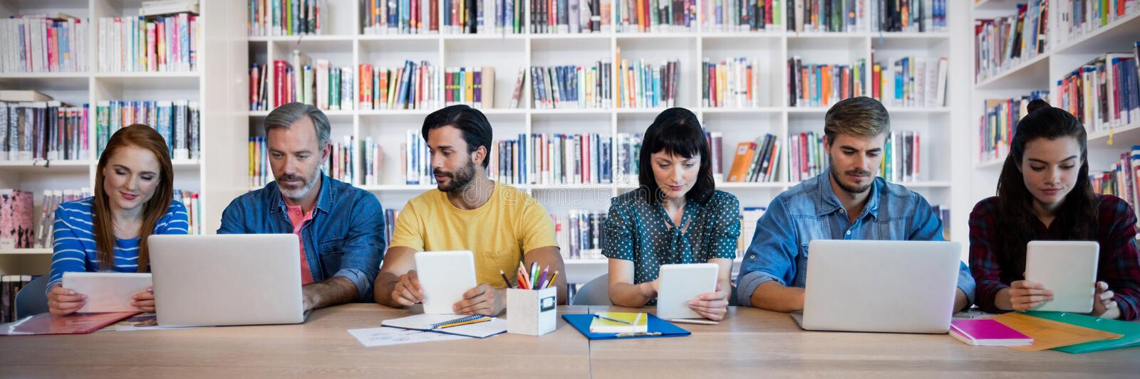 Composite image of business people working at table. Business people working at table against teacher reading books to her students stock photos
