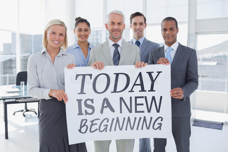 Composite image of business team holding large blank poster stock photography