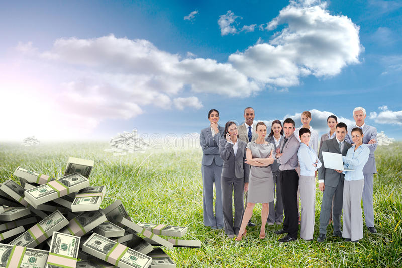 Composite image of business team looking at camera. Business team looking at camera against sunny landscape royalty free stock image