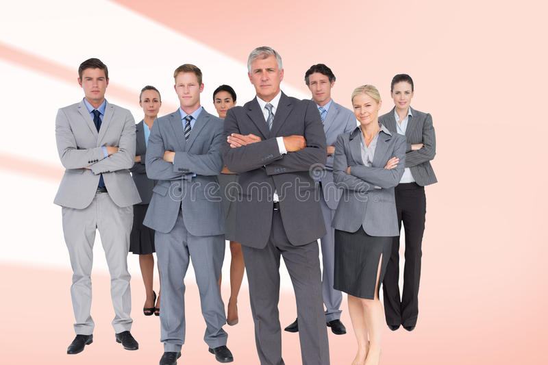 Composite image of business team standing arms crossed. Business team standing arms crossed against red vignette royalty free stock images