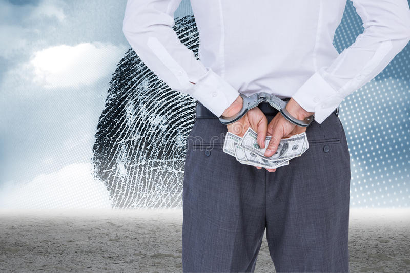 Composite image of businessman in handcuffs holding bribe. Businessman in handcuffs holding bribe against thumbprint graphic over desert stock photos