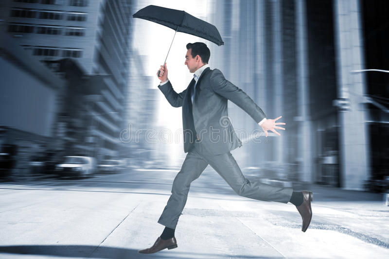 Composite image of businessman jumping holding an umbrella. Businessman jumping holding an umbrella against new york street stock photo