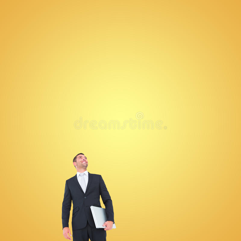 Composite image of businessman looking up holding laptop royalty free stock photography