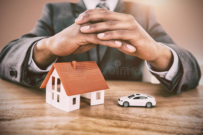 Composite image of businessman protecting house model and car with hands on table. Businessman protecting house model and car with hands on table against bright royalty free stock photo