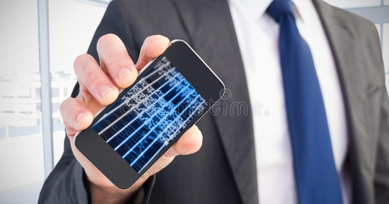 Composite image of businessman showing his smartphone screen. Businessman showing his smartphone screen against stocks and shares stock images