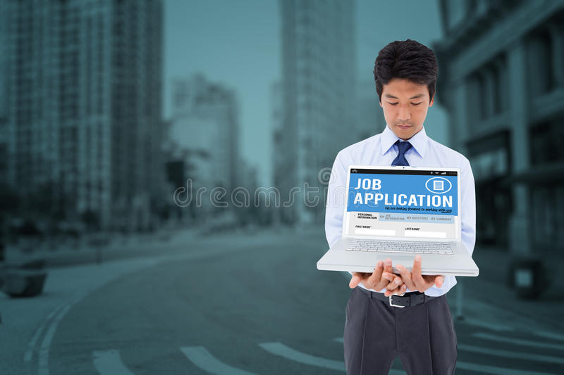 Composite image of businessman showing a laptop. Businessman showing a laptop against new york street stock image