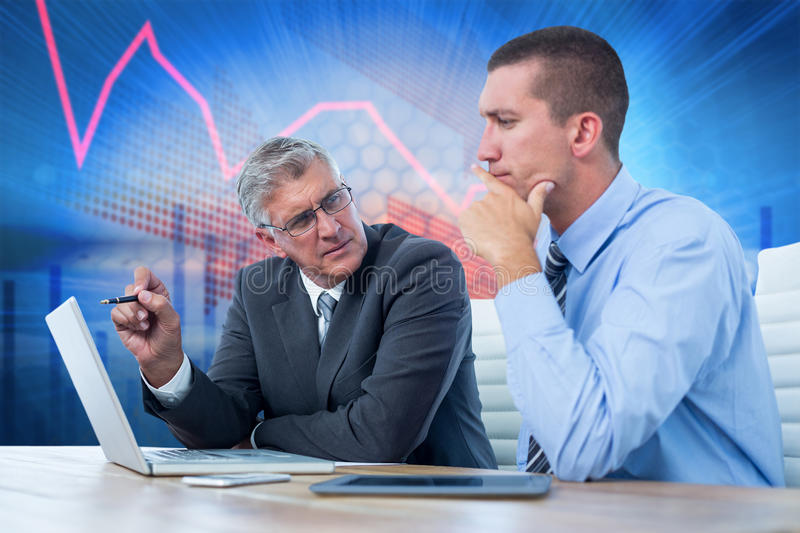 Composite image of businessmen working together with laptop and tablet. Businessmen working together with laptop and tablet against stocks and shares stock image