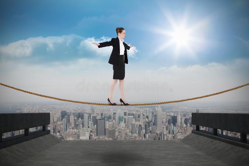 Composite image of businesswoman performing a balancing act royalty free stock image
