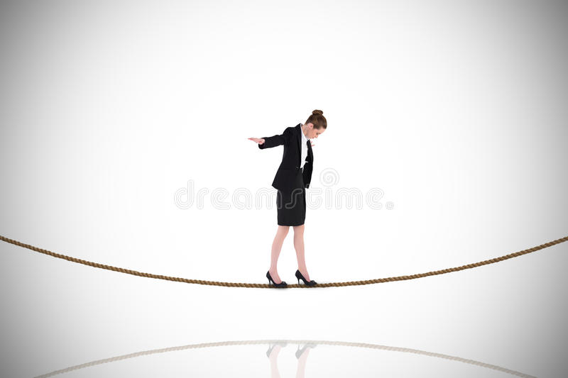 Composite image of businesswoman performing a balancing act on tightrope. Businesswoman performing a balancing act on tightrope against white background with royalty free stock image