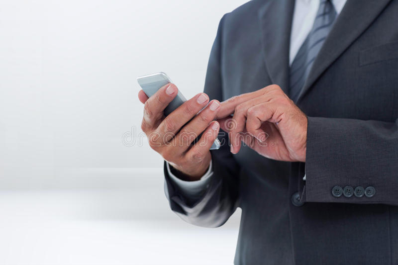 Composite image of businesswoman using smart phone. Businesswoman using smart phone against abstract white design royalty free stock photography