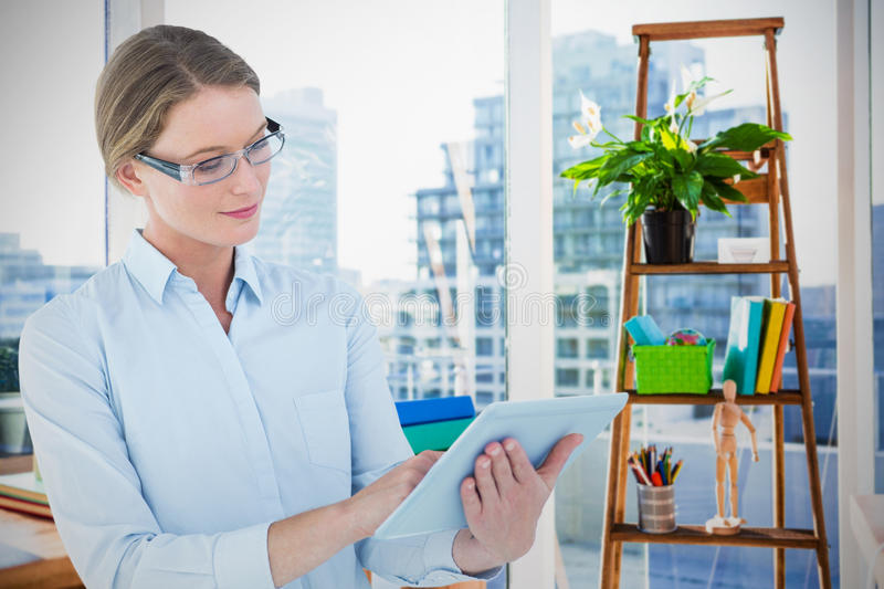 Composite image of businesswoman using tablet pc royalty free stock photo