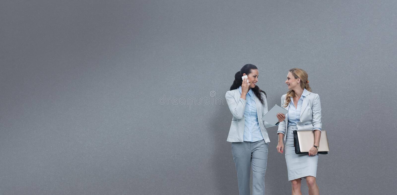 Composite image of businesswomen using mobile phone while walking stock photography
