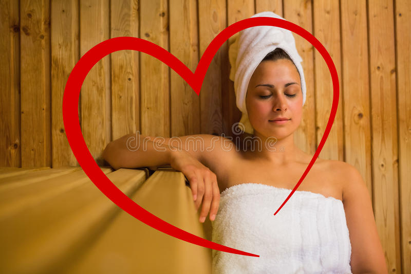 Composite image of calm woman relaxing in a sauna. Calm woman relaxing in a sauna against heart royalty free stock photo