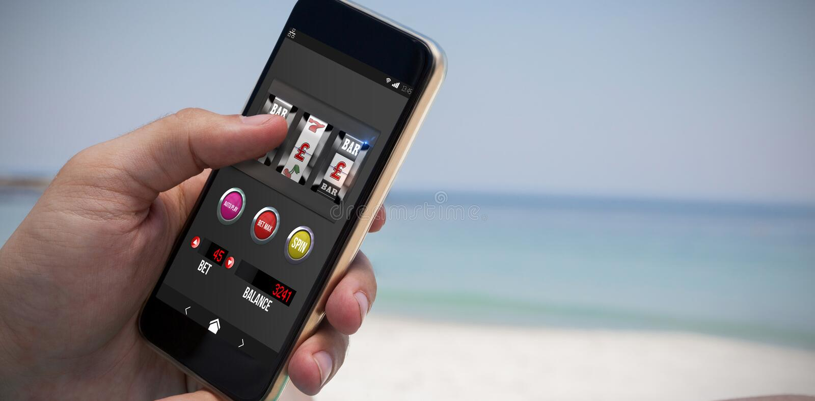 Composite image of casino slot machine on mobile display. Casino slot machine on mobile display against close up of man using smartphone at beach stock image
